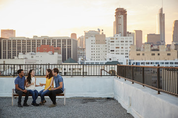 Friends Sitting On Rooftop Terrace Seat With City Skyline In Background