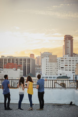 Rear View Of Friends On Rooftop Terrace Looking Out Over City Skyline At Sunset