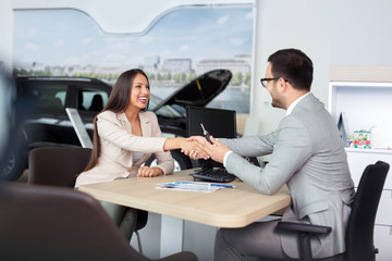 Car salesman giving the key of the new car to the young attractive girl