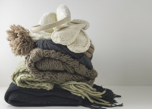 Warm woolen knitted winter and autumn clothes, folded in a pile on a white table. Sweaters, scarves, gloves, hat, headphones. Place for text. Copyspace.