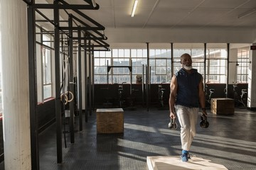 Senior man exercising with kettle bells in the fitness studio