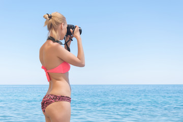 A female photographer in a swimsuit makes a photo on the sea, the ocean. Beach vacation, travel.