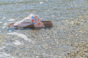 Gone in the ocean, the sea women's slippers. Lost shoes on vacation. The concept of the end of vacation, parting with the sea.