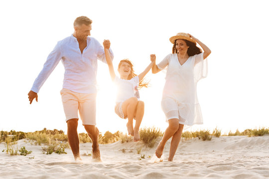 Cute family having fun together outdoors at the beach.