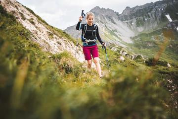 Adventurous Sportive Girl hiking in Beautiful Alpine Mountains Wall mural