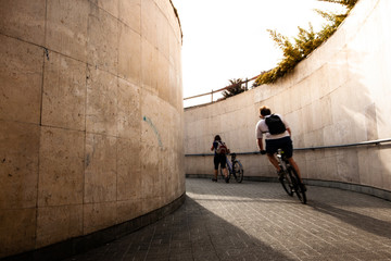 Man cycling in the city from underground during sunshine. Cyclist is motion blurred.