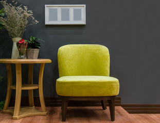 Modern yellow fabric chair and white wooden picture frame on black wall interior decoration