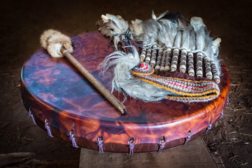 Feather headdress, ancient amerindian leather tambourine and drum drumstick. Attributes of the ancient american indian.