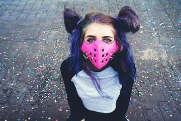 Chica joven con estilo urbano asiático y una máscara punk rosa con pinchos