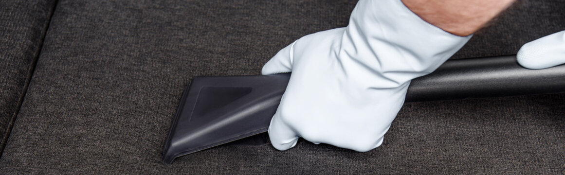 cropped shot of person in rubber gloves cleaning sofa with vacuum cleaner