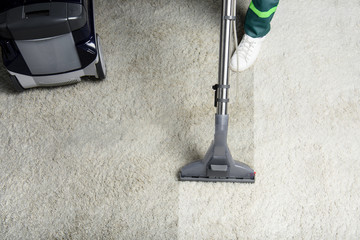 high angle view of person cleaning white carpet with professional vacuum cleaner
