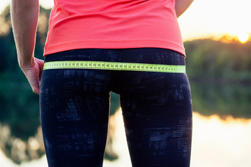 a sports woman measures the body's coverage with a measuring tape lake background diet idea