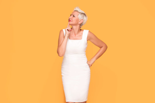 Beautiful woman posing on yellow background.