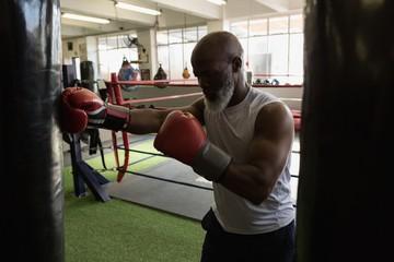 Senior man practicing boxing on the punching bag