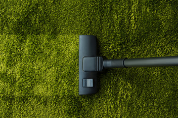 top view of vacuum cleaner cleaning green carpet