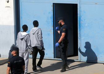 Migrants are led by a Spanish police officer into the new Center for Temporary Assistance to Foreigners after arriving at the port of Algeciras in San Roque