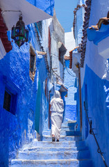 Photo sur Plexiglas Maroc Woman with white djellaba walking the blue streets of Chefchaouen, Morocco.