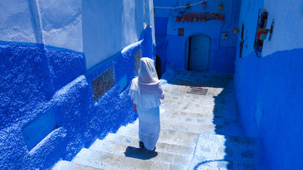 Woman with white djellaba walking the blue streets of Chefchaouen, Morocco.