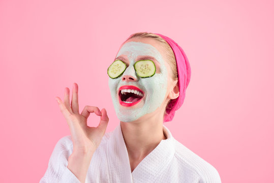 Close-up portrait of beautiful woman with facial mask. Spa salon. Cosmetic mask with cucumber. Natural beauty. Perfect skin. Woman with cucumber slices on eyes. Wellness and Spa concept. Sign okay.