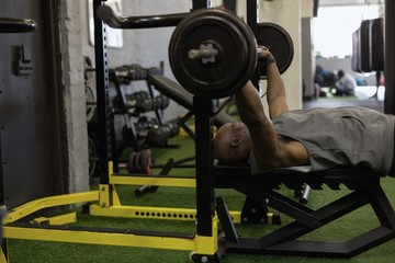Senior man exercising with barbell in the fitness studio