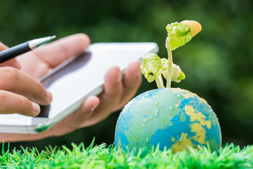 Student Hand holding smartphone for studying or researching seeding plant on Globe model in outdoor lab on sunny  green grass, Green save world environment ecology day, Life on earth concept
