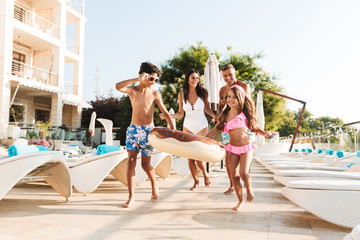 Image of happy caucasian family with children resting near luxury swimming pool, with white fashion deckchairs and umbrellas outside hotel