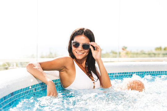 Portrait of smiling attractive woman in white bathing suit and sunglasses sitting in swimming pool, outdoor in spa resort