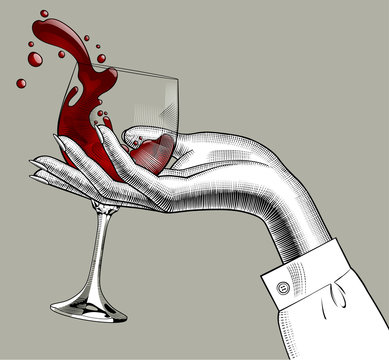 Woman's hand holding a glass with red splashed wine