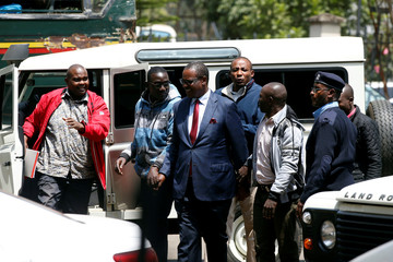 Evans Kidero, former governor of Nairobi, is escorted by police as he arrives to face charges over suspicion of corruption-related crimes at the Mililani Court in Nairobi