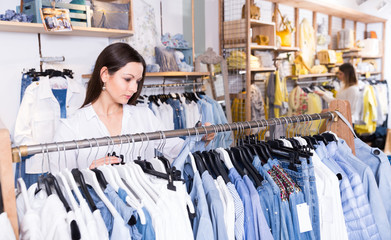 Woman customer choosing blue blouse   in the fashion store