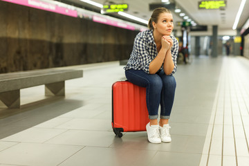 Woman sitting on suitcase at metro station