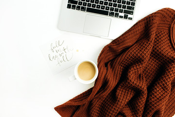 "Workspace with hand lettered quote ""Fall in love with fall"", laptop, coffee, warm pullover on white background. Flat lay, top view autumn office desk."
