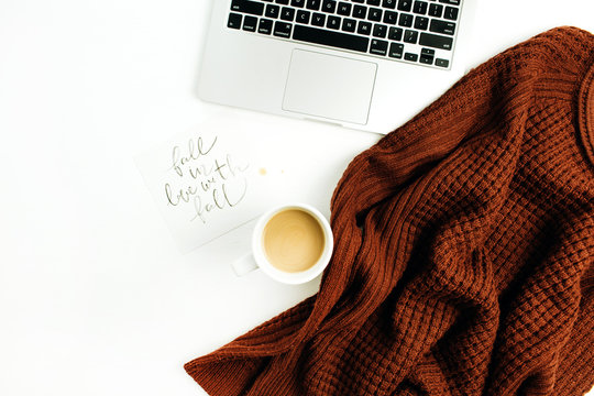 """Workspace with hand lettered quote """"Fall in love with fall"""", laptop, coffee, warm pullover on white background. Flat lay, top view autumn office desk."""