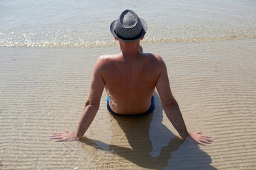 Summer lifestyle portrait of pretty young suntanned man in a hat. Enjoying life and sitting on the beach, time to travel. Looking at the sea