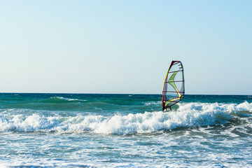 Windsurfers in the sea on Crete on sunset. Windsurfing in Heraklion