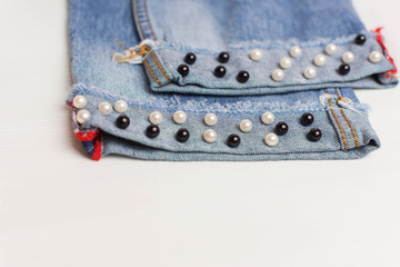 The design of jeans. Beads in the form of pearls are sewn to the jeans. Fashionable jeans.