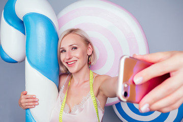 beautiful young blonde Barbie sweet woman confectioner sexy model perfect makeup hug a huge lollipop with measuring tape and take pictures selfie on phone background fake sweets candy in studio shot