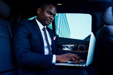 Handsome successful rich african american businessmen in a stylish black business suit and tie sitting in a luxury car and works with laptop. concept of luck and career growth