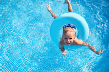 Child with toy ring in swimming pool. Sunny day, relaxing and having fun
