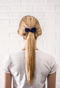 Women's hairstyle tail with a blue knitted bow back view