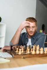 handsome pensive man looking at chessboard at home