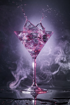 cocktail martini splashing isolated in a smoky grey background