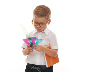 Back to school - Cute Little boy with blond hair in glasses standing with his office supplies for school. Place for text