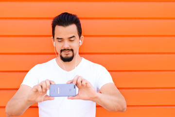 Young man with beard and moustache taking a picture on his smartphone while listening to music via earphones against orange wall.