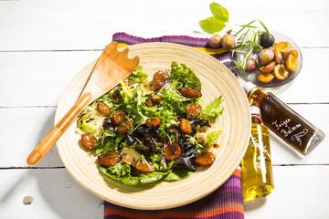 Salat mit gedünsteten Honig-Balsamico-Zwetschken (Zwetschgen), Champignons, Mandeln und Kresse auf Holzteller serviert