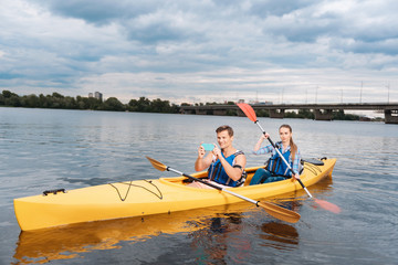 Picture of landscape. Handsome man sitting in kayak with his beautiful woman taking picture of nice landscape