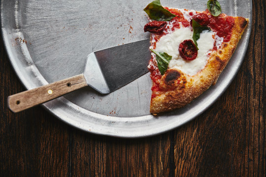 top view of slice of tasty pizza with server on metal tray and wooden table