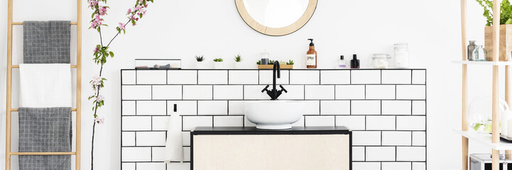 Real photo of white bathroom interior with wooden ladder with towels, tiles on wall shelf with plants and cosmetics and white sink on cabinet