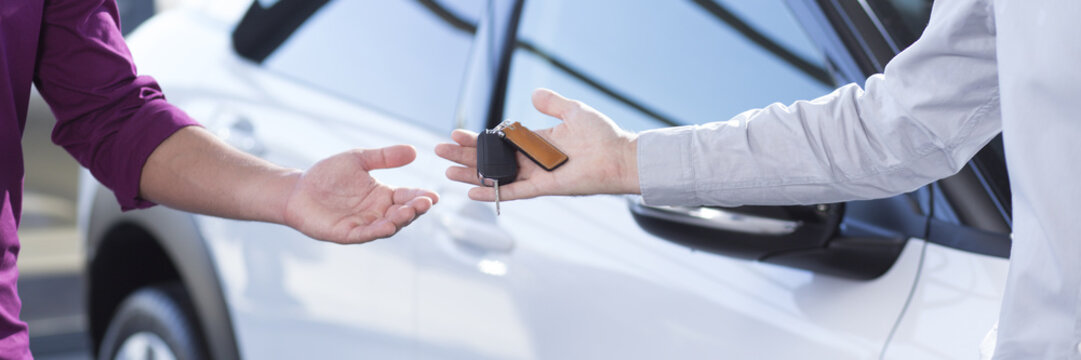 Panorama and close-up of car seller's hand with keys and buyer's hand after transaction