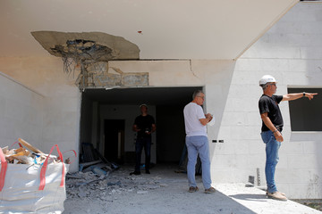 People survey the damage to a construction site where a rocket exploded, in the southern city of Sderot